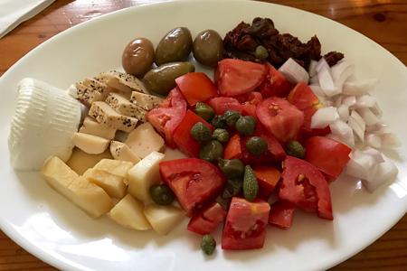Platte mit Tomaten, Käse, Oliven, Kapern