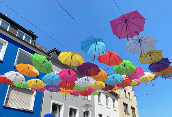 Bunte Schirme vor blauem Haus